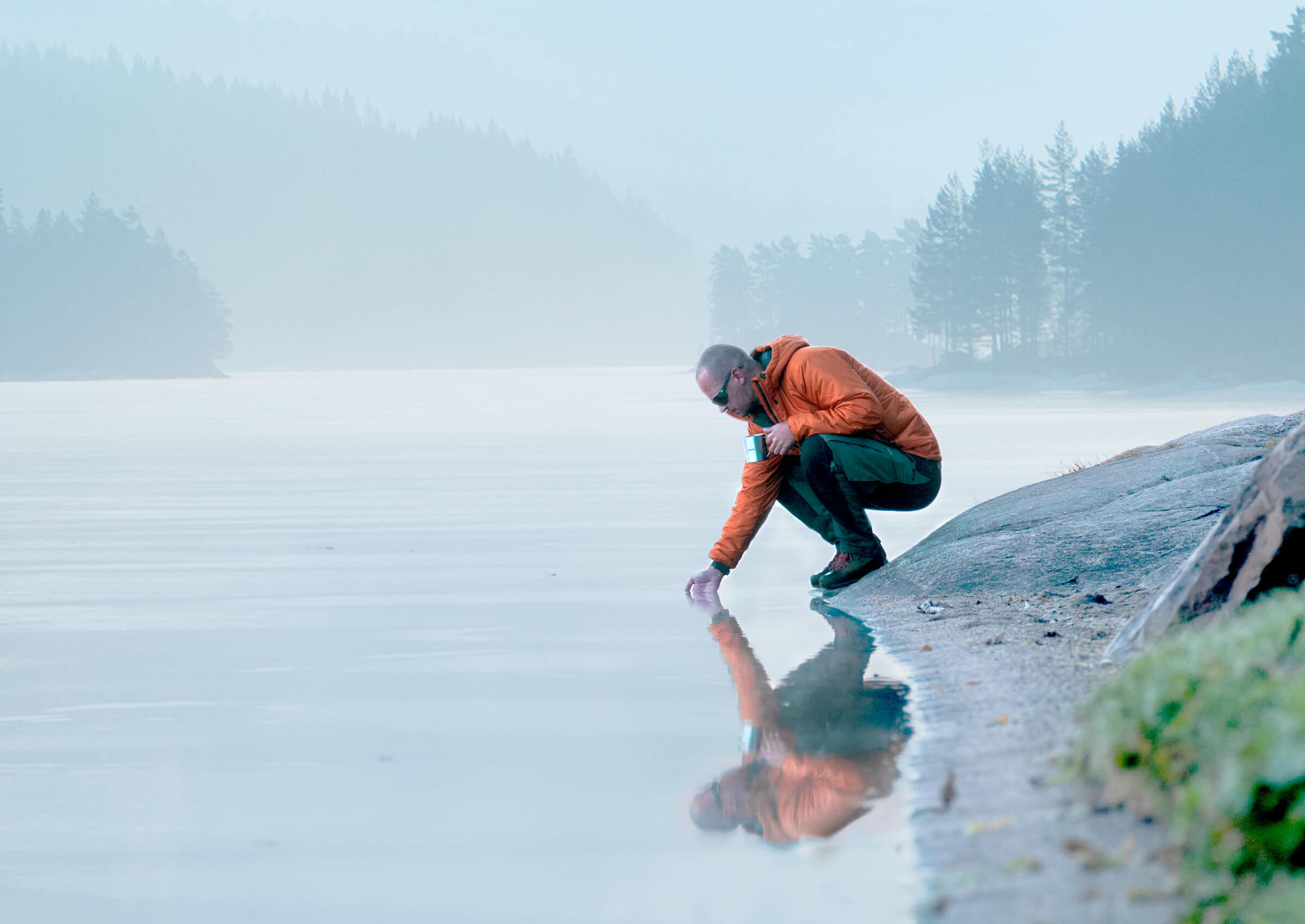 Man kneeling by a lake
